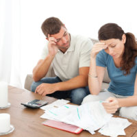 Worried couple doing their accounts in the living room at home