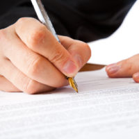 Close up on a businessman hands signing a contract. Isolated on white background